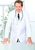 Doutor sênior bem sucedido Standing Tabela Fotos de Stock Royalty Free