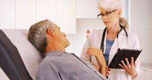 Doutor superior da mulher que fala com o paciente idoso do homem no escritório Fotos de Stock Royalty Free