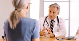Doutor superior que discute o procedimento da cirurgia com o paciente idoso da mulher fotografia de stock