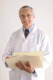 Doutor Terra arrendada Dobrador com carta de pacientes Imagem de Stock Royalty Free