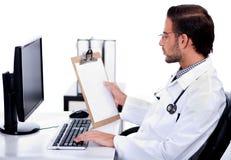 Doutor étnico novo que olha médico Fotografia de Stock