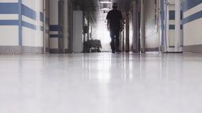 Doutor Walking através do corredor escuro vídeos de arquivo