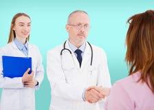 Doutores com o paciente fêmea isolado no fundo azul, contrato médico fotografia de stock royalty free