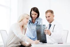 Doutores com o paciente que olha o raio X imagem de stock royalty free