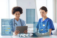 Doutores com PC e prancheta da tabuleta no hospital Foto de Stock Royalty Free