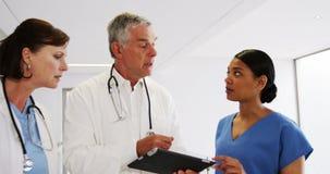 Doutores e enfermeira que discutem sobre a tabuleta digital filme