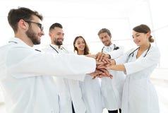 Doutores e enfermeiras em uma equipa médica que empilha as mãos Foto de Stock Royalty Free