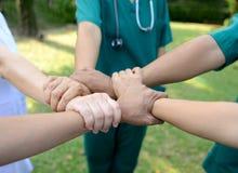 Doutores e enfermeiras em uma equipa médica que empilha as mãos exteriores em t Foto de Stock