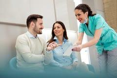 Doutores e pacientes que falam na sala de espera do hospital imagem de stock