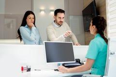 Doutores e pacientes que falam na sala de espera do hospital fotografia de stock
