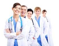 Doutores felizes em vestidos do hospital na fileira imagem de stock royalty free
