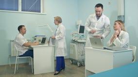Doutores masculinos e fêmeas que discutem casos médicos no escritório filme