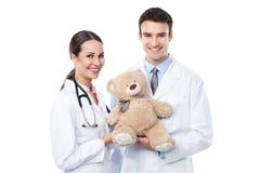 Doutores pediatras que guardam o urso de peluche imagens de stock