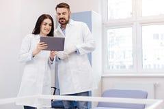 Doutores profissionais positivos que trabalham com uma tabuleta Fotografia de Stock