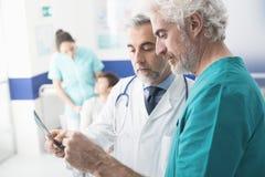 Doutores profissionais que examinam o raio X paciente do ` s fotos de stock royalty free