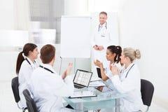 Doutores que aplaudem para o colega após a apresentação Fotografia de Stock