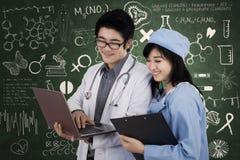 Doutores que discutem com o portátil no laboratório imagem de stock royalty free