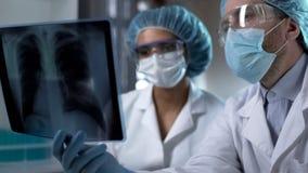 Doutores que estudam o raio X dos pulmões no laboratório, analisando e discutindo o diagnóstico imagem de stock