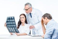 Doutores que examinam a imagem do raio X imagem de stock
