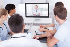 Doutores que olham a apresentação em linha