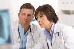 Doutores que olham a imagem do raio X imagens de stock royalty free