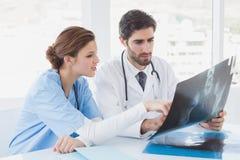 Doutores que sentam-se junto com raios X imagens de stock royalty free
