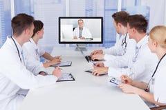 Doutores que têm a reunião da videoconferência no hospital