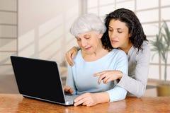 A doutrina da jovem mulher ensina a filha de um laptop idoso da mulher imagens de stock