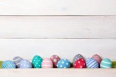 Douze oeufs de pâques faits main colorés se tiennent dans une rangée sur un fond en bois blanc avec l'espace d'en haut Image stock