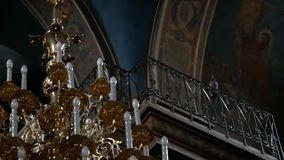 Dove sits on a railing under the ceiling inside the church. The bird takes off in the room. Big chandelier in the foreground stock video footage