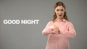 Dove vrouw die goede nacht in asl, tekst op achtergrond, mededeling voor doof zeggen stock footage