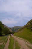 Dovedale Valley. Scenic view of people walking along track by lake in Dovedale Valley, Peak District, England Stock Image