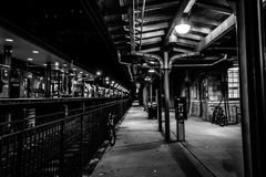 Dover, NJ USA - November 1, 2017:  Bicycles rest along the grungy train station at night, black and white Stock Images