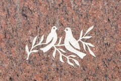 Doves and olive branch on stone surface. Symbol of peace Engraved on a memorial stone at Johannisfriedhof, Dresden, Germany royalty free stock photography