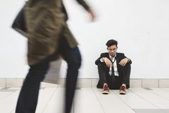 Dowdy young asian businessman sitting at walkway thinking of his problem stock photo