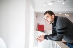 Dowm bello di sguardo dell'uomo dalla barriera delle scale con il sorriso Fotografia Stock