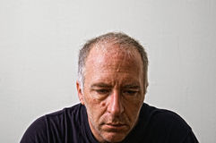 Down. Beautifully detailed real portrait of mature unkempt looking adult white man looking down in serious thought Stock Photos