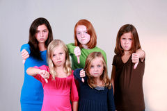 Down With That. Diverse group of pretty preteen girls giving thumbs down sign Stock Images