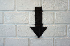 Down arrow sign on white brick wall Stock Image