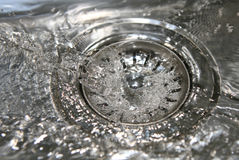 Down the Drain. Close-up of clean water running down the plug hole of a stainless steel sink Royalty Free Stock Images