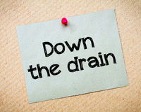 Down the drain. Message. Recycled paper note pinned on cork board. Concept Image Royalty Free Stock Photography