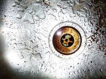 Down The Plug Hole. Plug Hole with waterdrops around it Royalty Free Stock Image