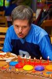 Down-Syndrom Mann brennt heraus Geburtstags-Kerzen durch lizenzfreies stockbild