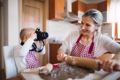 A down syndrome boy with a camera and his mother indoors baking. stock photo