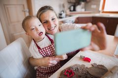 A down syndrome boy with his mother indoors taking selfie when baking. stock photo