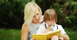 Down syndrome boy with mother reading book. Little boy suffering down syndrome spending time outdoors and reading english book, education stock video