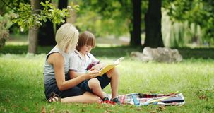 Down syndrome boy with mother reading book. Young blonde lady and little Down syndrome boy sitting in park and reading book, education and development stock footage