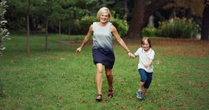 Down syndrome boy running in park. Middle-aged woman running with boy suffering down syndrome in park, importance of socialisation, love stock video footage