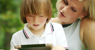 Down syndrome boy scrolling tablet with mother. Preteen Down syndrome boy in white shirt scrolling tablet with mother sitting in park, educational application stock footage
