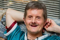 Down Syndrome Man No Teeth Leaning Back Smiling. A happy man with Down Syndrome leans back on a couch with a big smile. He is older, and has lost all his teeth royalty free stock image